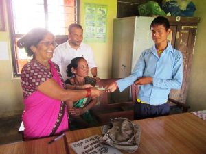 Avishek Tharu receiving money from headmaster